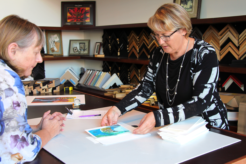 The MacLaren Art Centre's professional framer providing a free consultation for a customer.