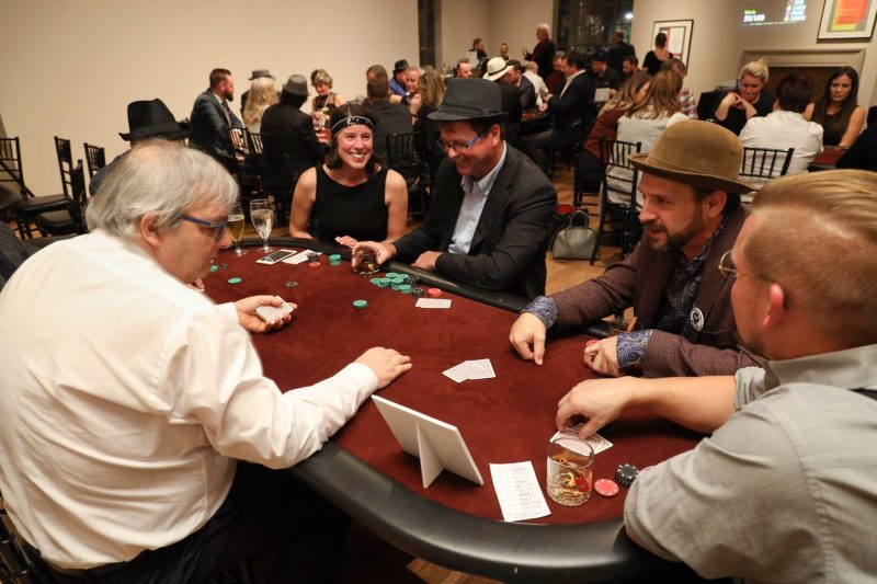 Adults playing poker at the MacLaren Art Centre's Speakeasy event