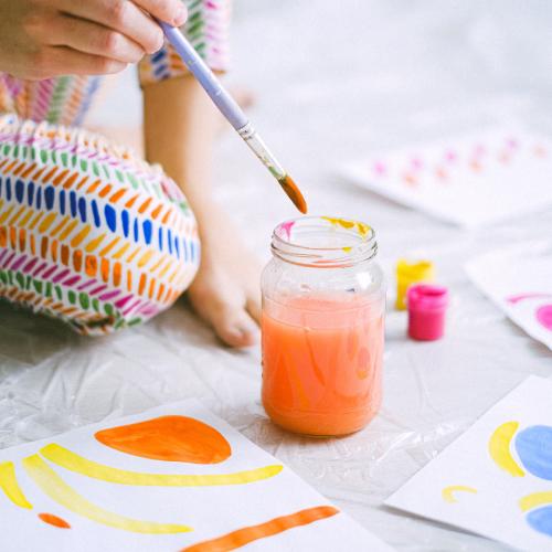 Child dipping paintbrush in jar