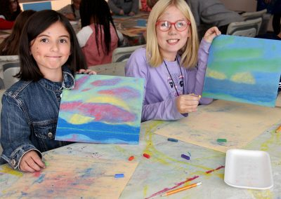 Two children showing artwork they made on a school field trip
