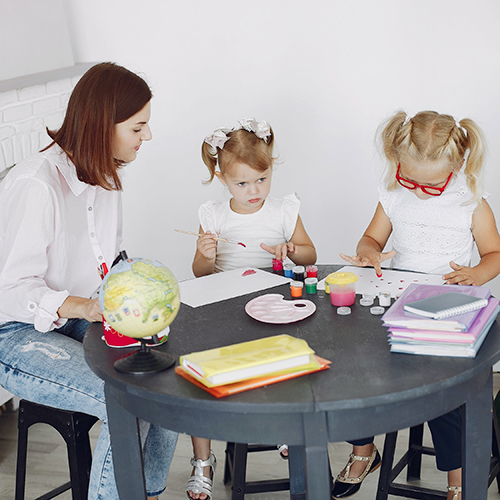 Mother and two children doing painting activity