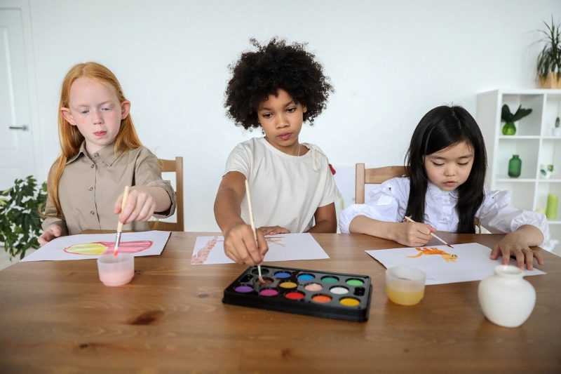 Three girls sitting at a table painting