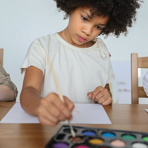 Child sitting at desk painting