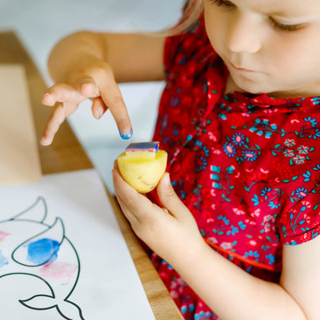 Child creating art with potato stamps