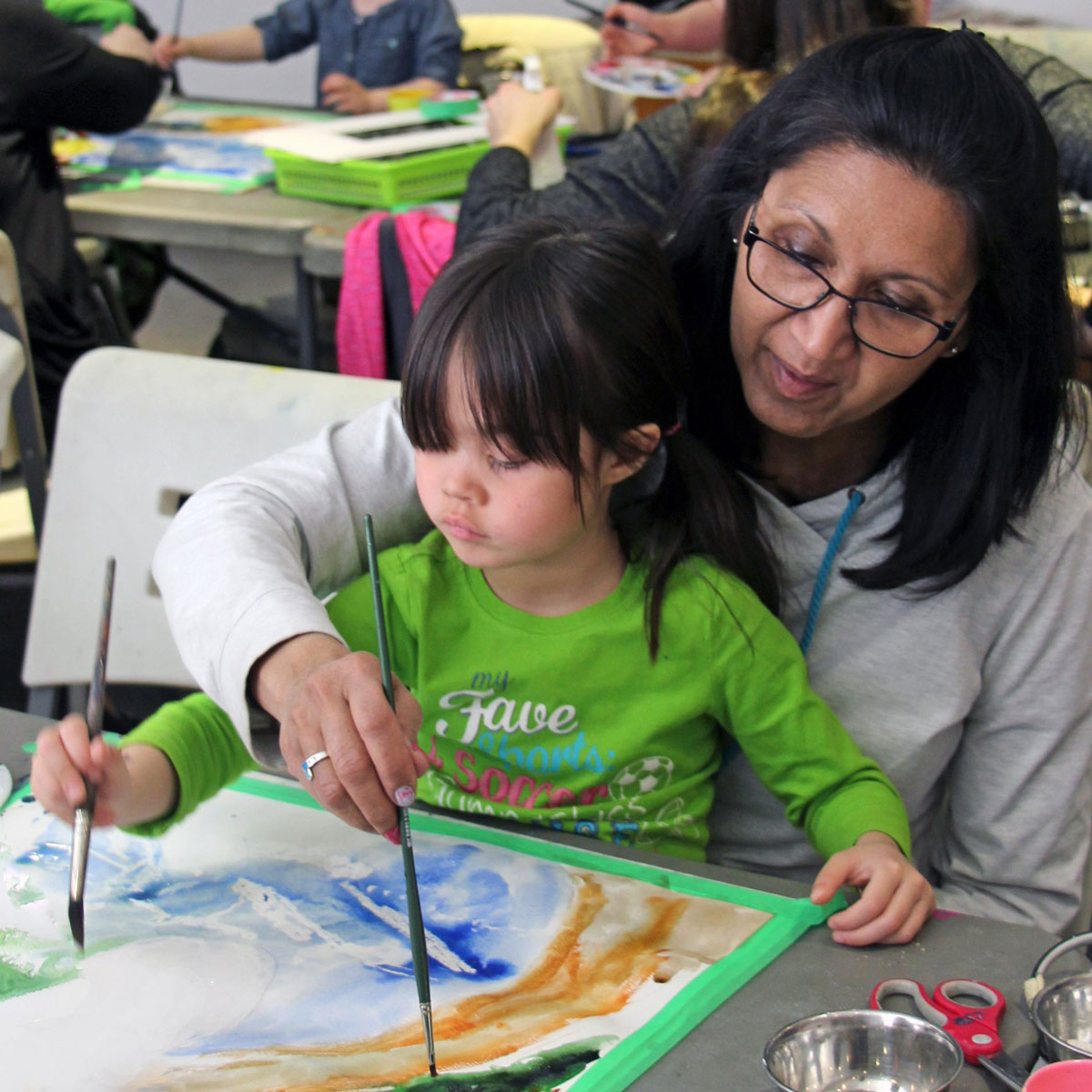 Mother and daughter creating artwork in family workshop